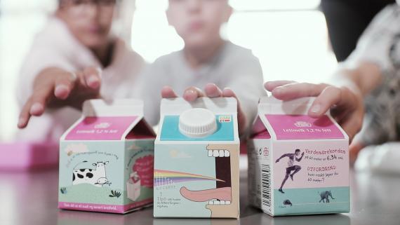 I forgrunnen tre skolemelk-kartonger, i bakgrunnen tre elever som strekker hendene mot kartongene