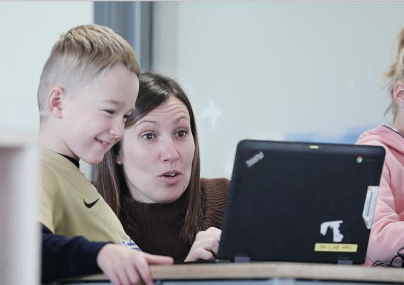 Bilde av blid gutt på ca. 8 år og lærer som ser sammen på dataskjerm.